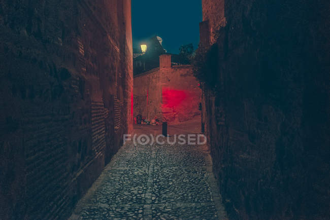 View to empty dark alley with red illumination at night. — Stock Photo