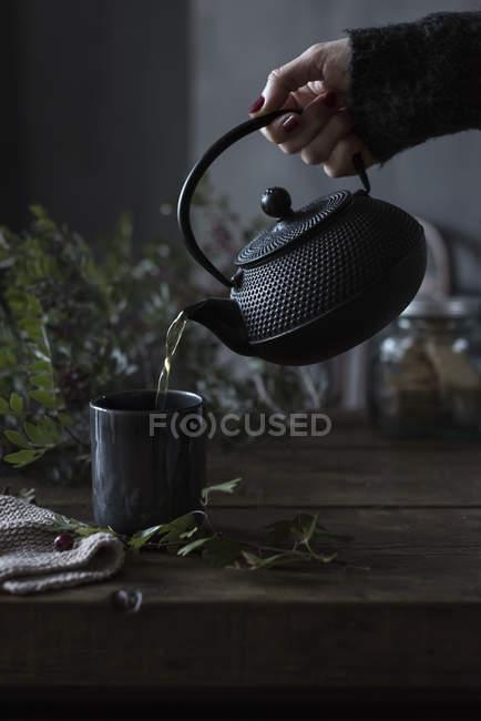 Main de cultures de thé versant oriental théière pour coupe sur table. — Photo de stock