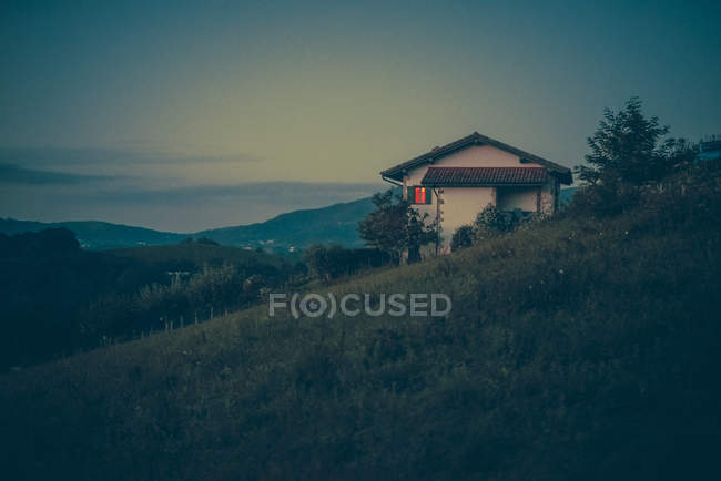 View to big house on grassy hill's slope in evening dusk. — Stock Photo