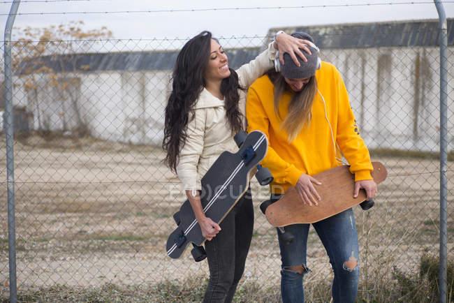 Две девушки с longboards, обманывают на уличная сцена — стоковое фото