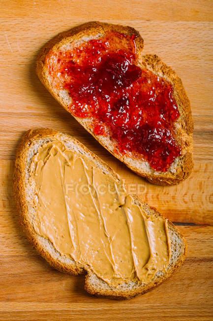 Vista directamente encima de la mantequilla de maní y jalea bocadillos en la mesa - foto de stock