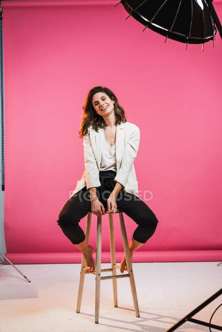 Усміхаючись брюнетка жінка, сидячи на стільці в студії — стокове фото