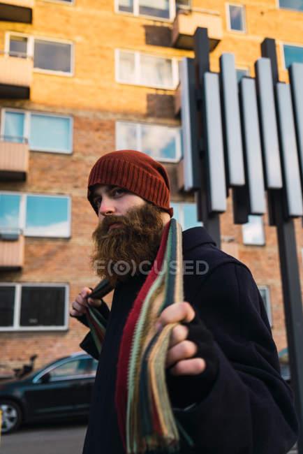 Вид сбоку босоногого мужчины, поправляющего шарф на улице — стоковое фото