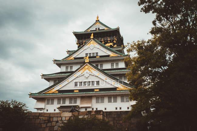 Vista exterior del templo oriental, colocado sobre cimientos de piedra entre los árboles - foto de stock