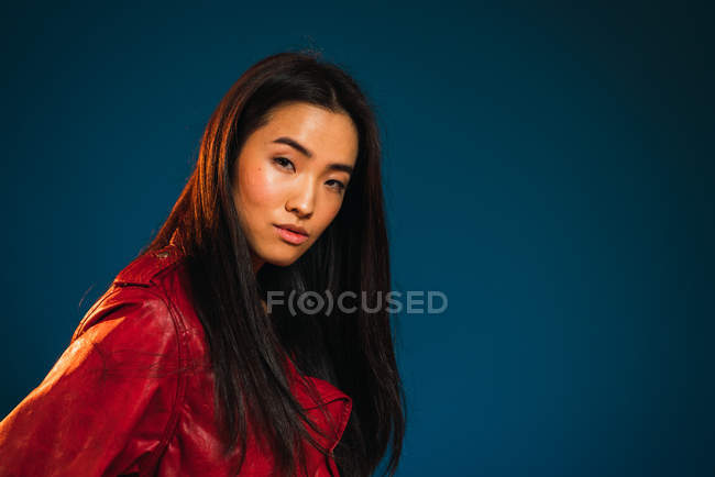 Portrait of young woman in stylish clothes posing on blue background. — Stock Photo