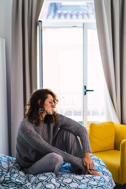 Vista lateral da mulher sentada na cama e olhando para baixo — Fotografia de Stock