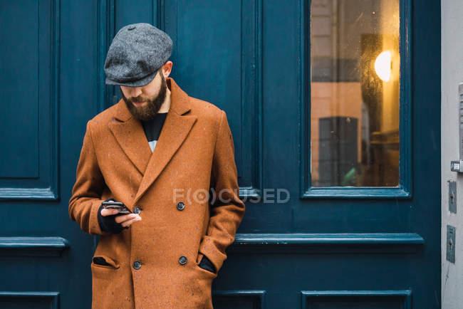 Pensativo homem elegante inclinando-se na porta e smartphone de navegação — Fotografia de Stock