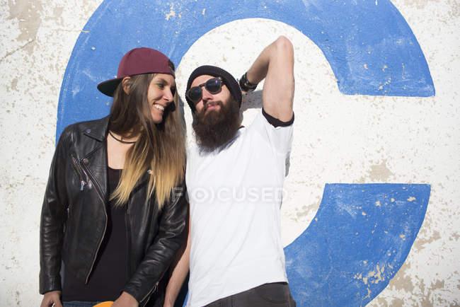 Молодая пара опирается на стену и позирует перед камерой — стоковое фото