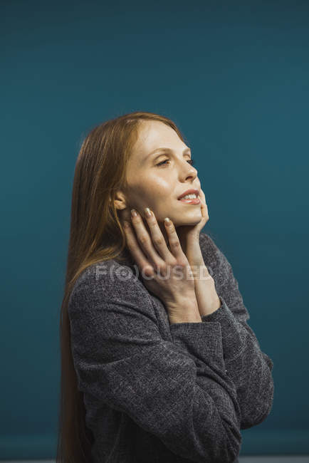Portrait of dreamy redhead woman touching face and looking away — Stock Photo
