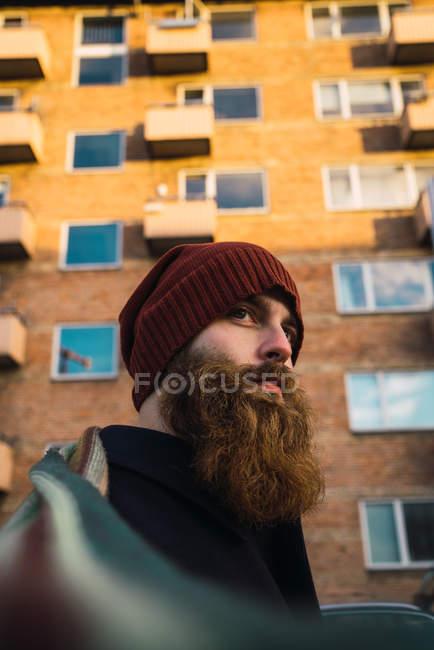 Ritratto dell'uomo barbuto in cappello che distoglie lo sguardo sulla strada — Foto stock