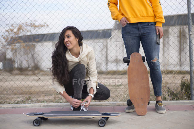 Two girls with longboards posing at street scene — Stock Photo