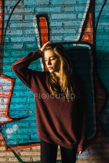 Young woman holding head and and leaning at brick wall with graffiti. — Stock Photo