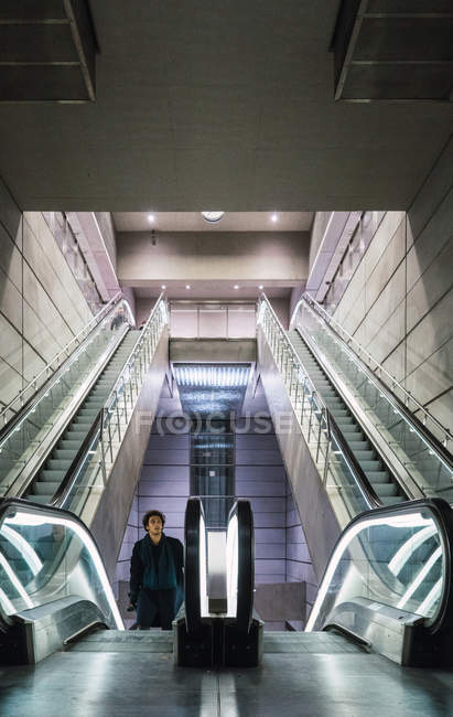 Portrait of man standing on moving stairs at mall — Stock Photo