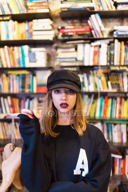 Portrait von junge Frau posiert mit Holzschuhe in Bibliothek und Blick in die Kamera — Stockfoto