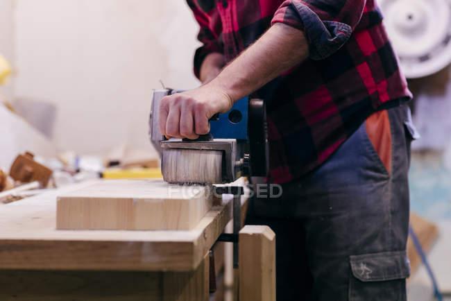 Mittelteil des Tischlers poliert Stück Holz in Werkstatt — Stockfoto