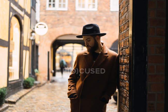 Стильний мужчина марочні одягу, спираючись на стіні арці — стокове фото