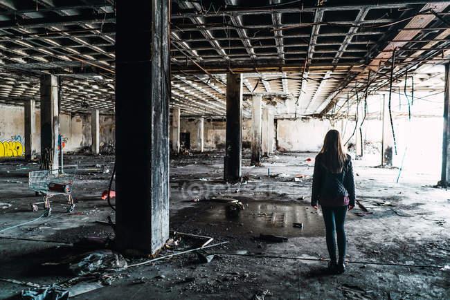 Vista posteriore di bella donna in piedi in mezzo alle intemperie camera abbandonata . — Foto stock