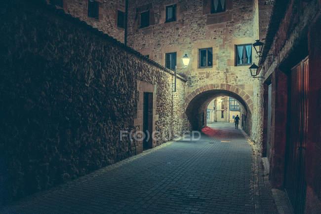 Переглянути до побудови фасад з аркою і пішохідних на вулиці вночі. — стокове фото