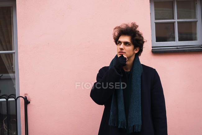 Портрет вдумливі молодий чоловік, торкаючись підборіддя і фотографіях хтось дивитися вбік на фоні рожевий стіни — стокове фото