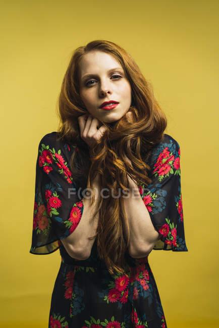Portrait of redhead woman holding hair and looking at camera on yellow background. — Stock Photo