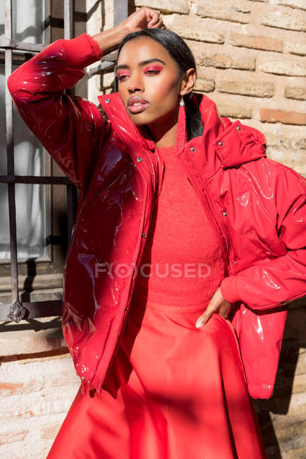 Fashionable woman in red clothes posing at window on street. — Stock Photo