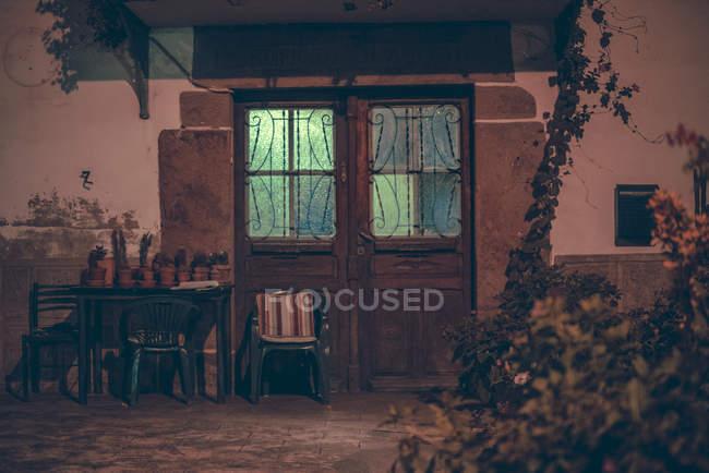 Esterno della facciata con tavolo e sedie da porta in legno con luce nell'edificio — Foto stock