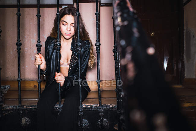 Portrait of young woman in jacket and bra posing at grid at home. — Stock Photo