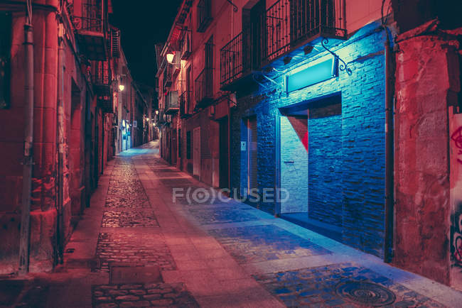 Perspective view to red and blue lit street facades — Stock Photo