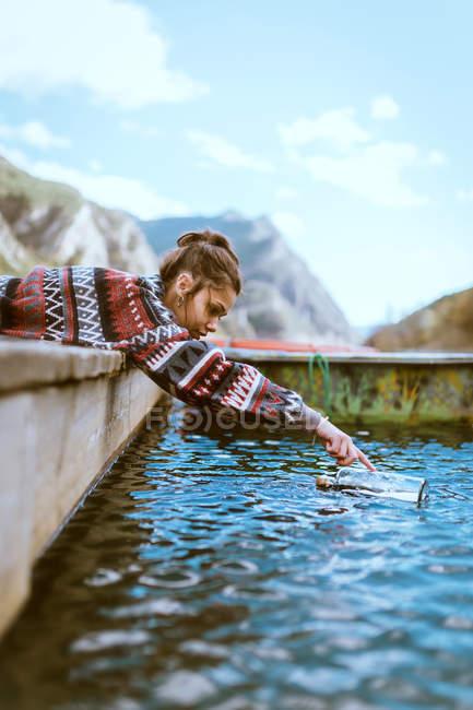 Вид збоку жінка лежить на дерев'яний причал і покласти склянний флакон з повідомленням у воді — стокове фото
