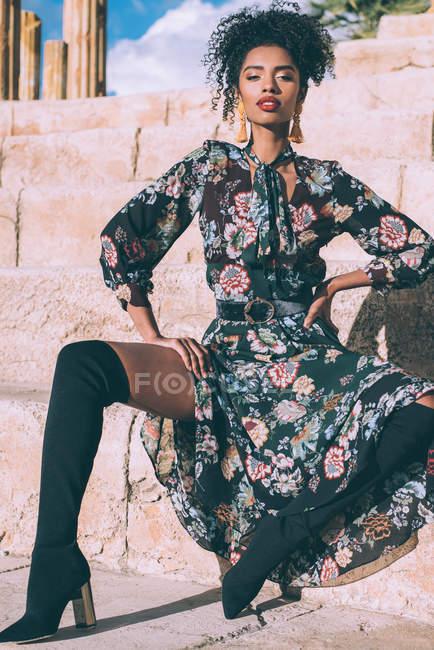 Giovane donna in abiti eleganti in posa su gradini di pietra . — Foto stock