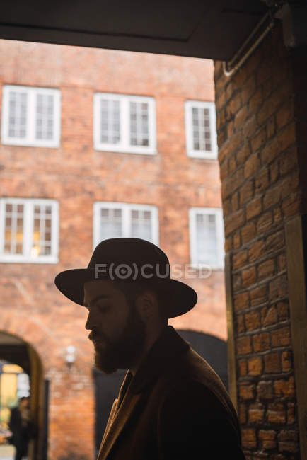 Stylish bearded man in hat leaning on wall at archway — Stock Photo