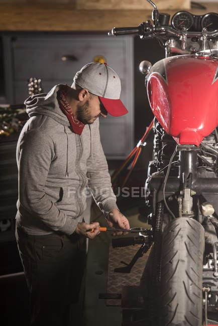 Vista lateral de reparación de motos en taller mecánico - foto de stock