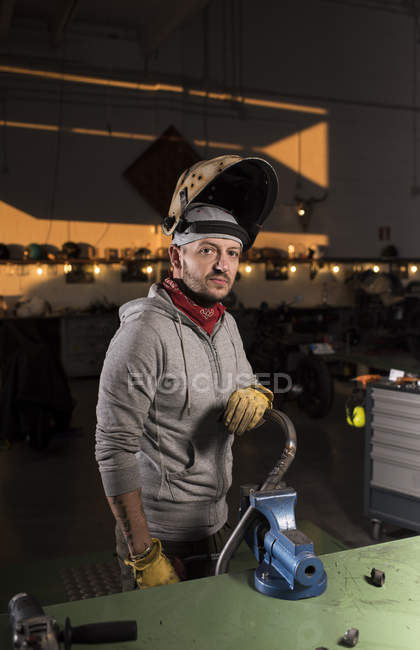 Porträt eines Mechanikers, der Kupplungen an der Werkbank in der Werkstatt benutzt und in die Kamera blickt — Stockfoto
