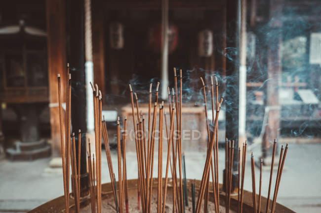 Bâtonnets d'encens brûlant de fumée au temple oriental — Photo de stock