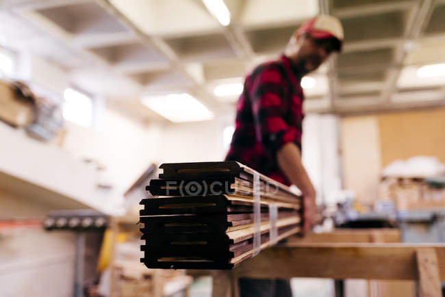 Blurred carpenter carrying stacked wood pieces at workshop — Stock Photo