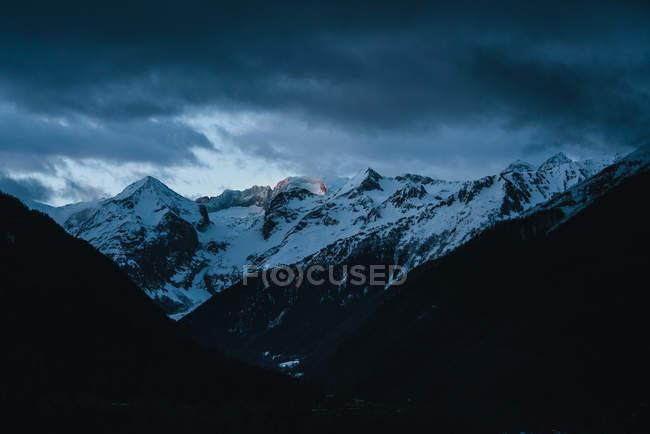 Vista para montanhas cobertas de neve sob céu nublado . — Fotografia de Stock
