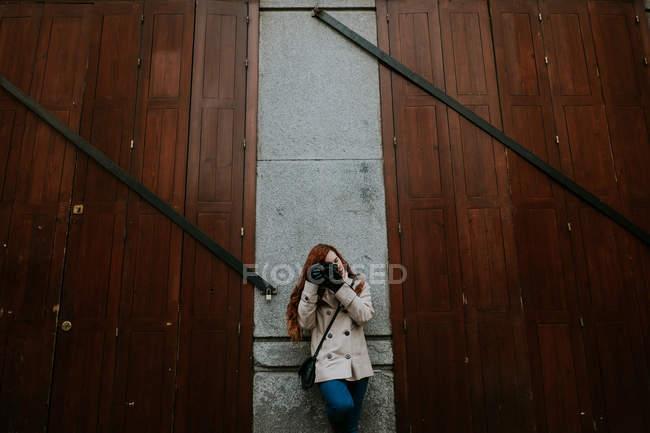 Femme rousse se penchant sur le mur tout en se concentrant avec caméra. — Photo de stock