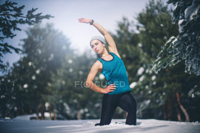 Portrait of fit woman standing in snow and bending aside to warm up muscles. — Stock Photo