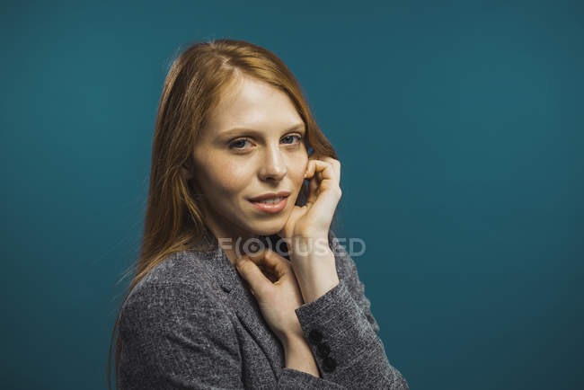 Portrait of redhead woman touching face and looking at camera — Stock Photo