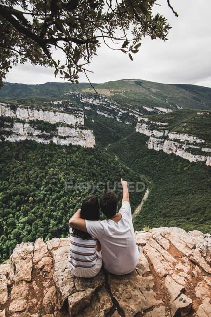 Rückansicht eines Paares, das auf einer Klippe sitzt und die Landschaft bewundert — Stockfoto