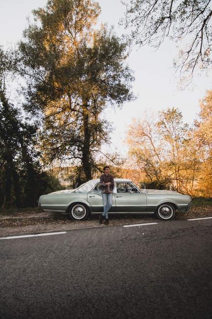Впевнено чоловік, спираючись на багажник автомобіля в країні придорожня — стокове фото