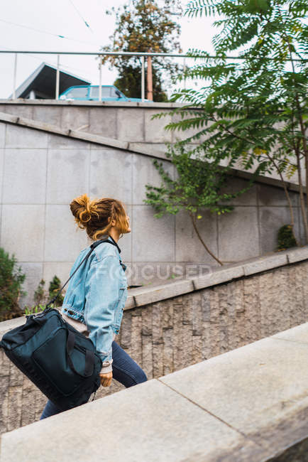 Side view of girl in denim jacket walking with travel bag at urban passage — Stock Photo