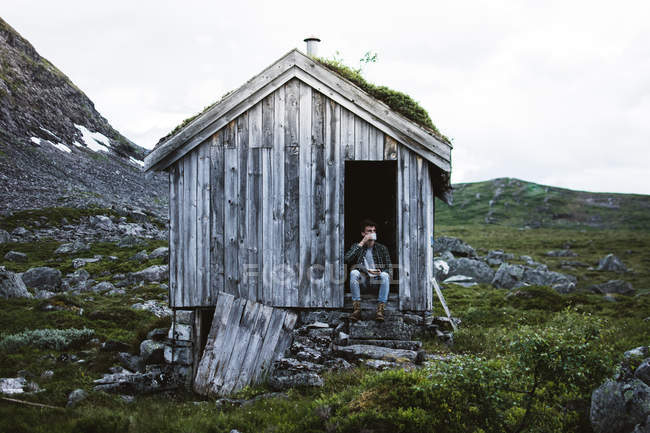 Homem sentado na porta da cabana gasto na natureza e beber café — Fotografia de Stock