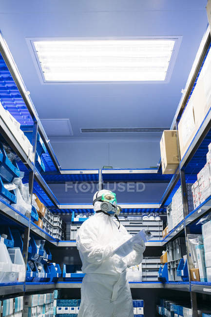 Scientist with papers standing in storage and doing revision in lab. — Stock Photo