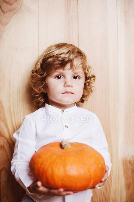 Застенчивый мальчик позирует с родными на деревянном заднем плане — стоковое фото