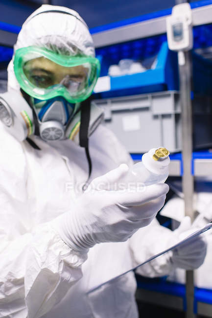 Researcher in white costume holding bottle in science lab. — Stock Photo