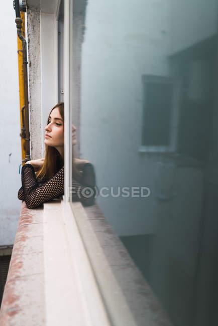 Giovane ragazza guardando fuori dalla finestra all'aperto — Foto stock
