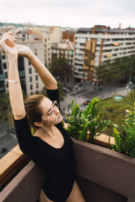Young girl in glasses outstretching arms on terrace — Stock Photo