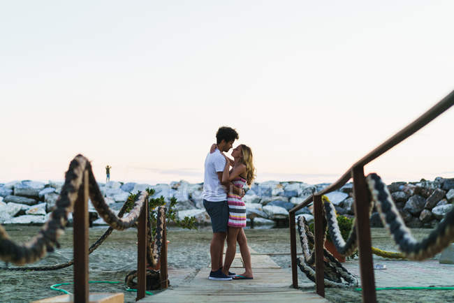Side view of young people embracing romantically on coastline and looking at each other. — Stock Photo