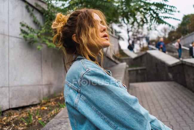 Retrato de morena em pé de jaqueta jeans por cerca — Fotografia de Stock